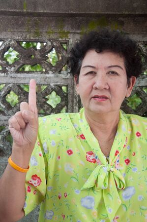 asian senior thai woman - point upward hand sign concept photo