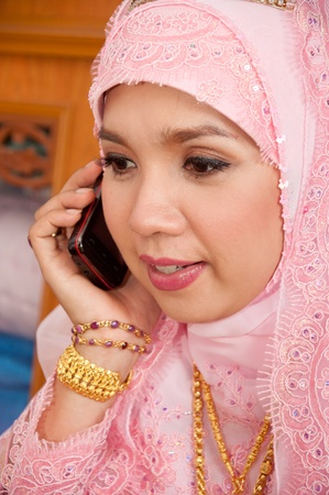 asian thai attractive muslim women in wedding suit talking phone