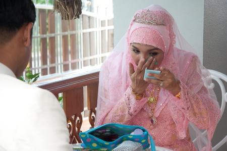 asian thai attractive muslim women in wedding suit making up Editorial
