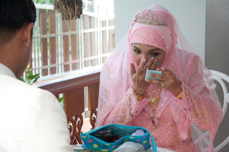 asian thai attractive muslim women in wedding suit making up Editorial