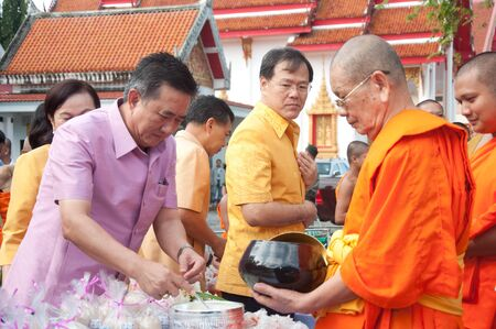 YALA, THAILAND - OCTOBER 22:Mr.Wittaya Panichphong  gives food offerings to monk in blessing ceremony for H.M.K. Bhumibol Adulyadej Birthday ceremony on Oct 22, 2011 at Yala Puttaphum Temple, Thailand Stock Photo - 11653449