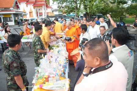 YALA, THAILAND - OCTOBER 22:Mr.Krissada Boonrach gives food offerings to monk in blessing ceremony for H.M.K. Bhumibol Adulyadej Birthday ceremony on Oct 22, 2011 at Yala Puttaphum Temple, Thailand Stock Photo - 11653529