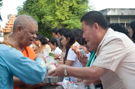 YALA, THAILAND - OCTOBER 22:Mr.Suchat Suwannakas gives food offerings to monk in blessing ceremony for H.M.K. Bhumibol Adulyadej Birthday ceremony on Oct 22, 2011 at Yala Puttaphum Temple, Thailand Stock Photo - 11653417