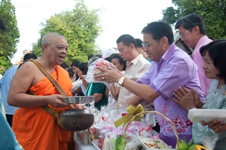 YALA, THAILAND - OCTOBER 22:Mr.Weeraphong Kaewsuwan gives food offering to monk in blessing ceremony for H.M.K. Bhumibol Adulyadej Birthday ceremony on Oct 22, 2011 at Yala Puttaphum Temple, Thailand Stock Photo - 11653451