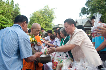YALA, THAILAND - OCTOBER 22:Mr.Suchat Suwannakas gives food offerings to monk in blessing ceremony for H.M.K. Bhumibol Adulyadej Birthday ceremony on Oct 22, 2011 at Yala Puttaphum Temple, Thailand Stock Photo - 11653454