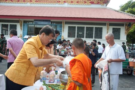 YALA, THAILAND - OCTOBER 22:Mr.Apinan Suethanywong gives food offerings to monk in blessing ceremony for H.M.K. Bhumibol Adulyadej Birthday ceremony on Oct 22, 2011 at Yala Puttaphum Temple, Thailand Stock Photo - 11653480
