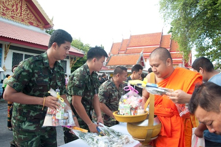 YALA, THAILAND - OCTOBER 22:Unidentified soldier gives food offerings to monk in blessing ceremony for H.M.K. Bhumibol Adulyadej Birthday ceremony on Oct 22, 2011 at Yala Puttaphum Temple, Thailand Stock Photo - 11653465