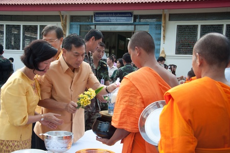 YALA, THAILAND - OCTOBER 22:Mr.Nuttaphong Sirichana gives food offering to monk in blessing ceremony for H.M.K. Bhumibol Adulyadej Birthday ceremony on Oct 22, 2011 at Yala Puttaphum Temple, Thailand Stock Photo - 11653436
