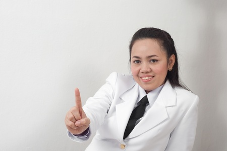 asian thai young business woman in white dress pointing finger up photo