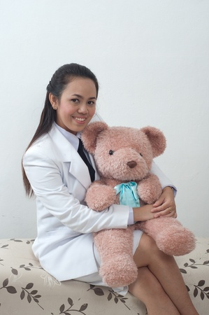 asian thai young business woman in white dress - hugging bear doll photo