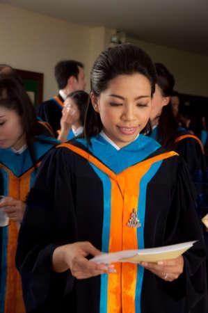 smiling asian attractive graduate college student woman in white unifom