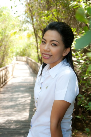 smiling asian attractive college student woman in white unifom