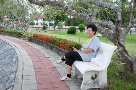 asian senior woman sitting on chair in garden