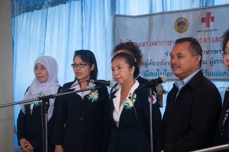 YALA, THAILAND - AUGUST 10: Mrs.Anongsri Simsiri (Center) Yala Red Cross President sings song in Queen Sirikit food give to female prisoners on Aug 10, 2012 at Yala Department of Corrections, Thailand Stock Photo - 15837423