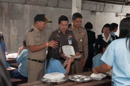 prisoner of love: YALA, THAILAND - AUGUST 10: Unidentified Police man gives food to a female prisoner in Queen Sirikit food give to female prisoners on Aug 10, 2012 at Yala Department of Corrections, Thailand