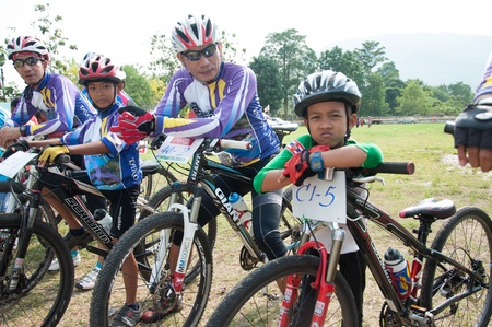 waits: YALA, THAILAND - APRIL 1: Unidentified boy waits on his mountain bike for race in Krongpinang Mountain Bike Racing on Apr 1, 2012 at  Yala Krongpinang district office, Thailand