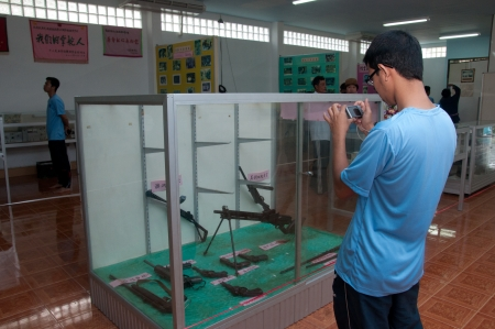 YALA, THAILAND-SEPTEMBER 22: Unidentified tourist take a picture of old guns Inside chinese museum on Sep 22, 2012 at Yala No.9 Chulaporn Development Village, Thailand Stock Photo - 16284893