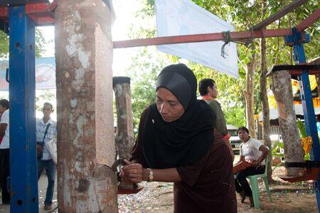 slit: YALA, Tailandia - 29 de agosto: Unidentified hendidura mujer musulmana �rbol de goma para la competencia hendidura del �rbol de goma en el festival de Yala d�a fruta el 29 de Ago de 2012 a Yala Kwan Jard�n Muang, Tailandia Editorial