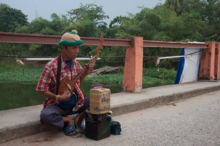 mendicant: SONGKHLA, THAILAND - AUGUST 11 : Unidentified male thai traditional musician play music for money donation for his child on Aug 11, 2012 at Songkhla Klonghae water market, Thailand
