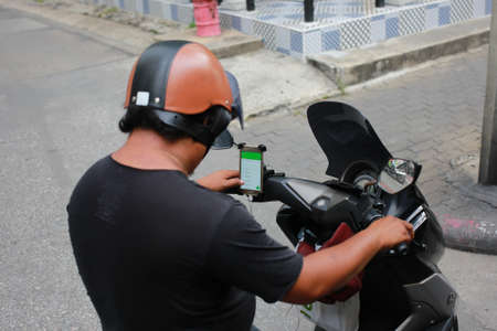 september 2: Bangkok, Thailand - September 2, 2016: A man is using Line when drive motorcycle. Smart phone can tell place and location to go anywhere. They replace paper map nowaday.