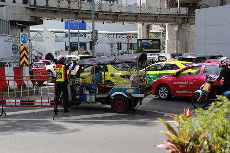 grasp: Bangkok, Thailand - September 2, 2016: Tuk Tuk (Thai 3 Wheels transportation car) get busted by traffic police. Traffic Police in Thailand always catch people who make mistake in traffic rule. Editorial