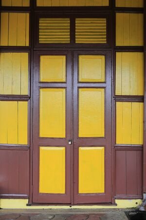 old vintage wooden style doors with mustard yellow painted color
