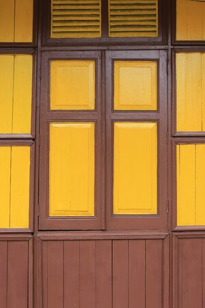 old vintage wooden style windows with mustard yellow painted color