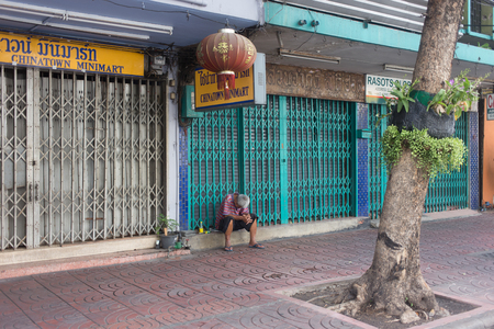 sit down: BANGKOK, THAILAND - SEPTEMBER 25, 2016. Old man sit down in front of Chinatown Minimart at Yaowarat Thai Chinna Town in Bangkok - Thailand Editorial
