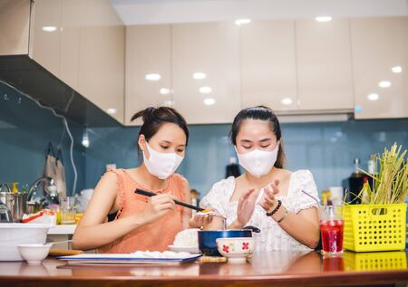 two young women cooking the tapioca dumpling in quarantine for coronavirus wearing protective mask during covid-19 pandemic