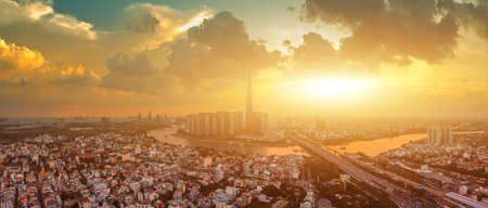 Panorama aerial view at Landmark 81 is a super tall skyscraper in center Ho Chi Minh City, Vietnam and Saigon bridge with development buildings, energy power infrastructure. Sunset in Ho Chi Minh city.