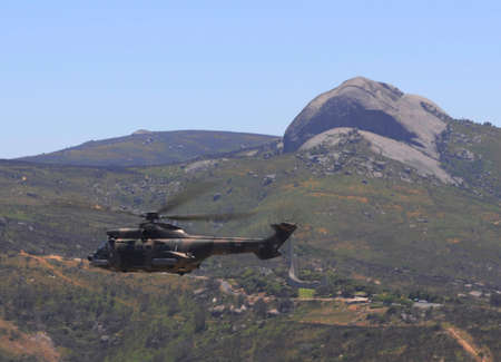 South African Airforce helicopter, the Oryx, flies past Paarl Rock and the Language Monument