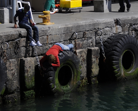 Children fishing off harbour wall, Kalk Bay, Cape Town South Africa
