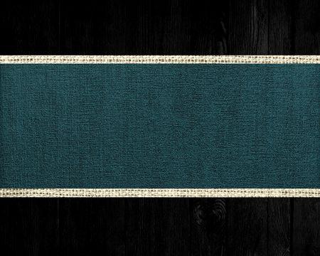 jungle green: Selva oscura de yute verde bandera lienzo textura con el fondo de madera oscura