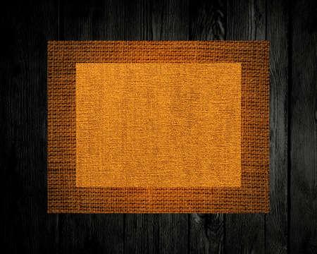 hessian: Burlap linen rustic canvas textured on dark wood background