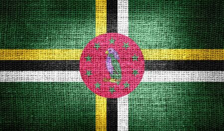 dominica: Dominica flag on burlap fabric Stock Photo