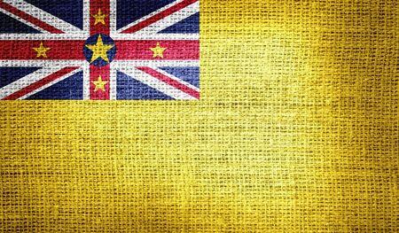 niue: Niue flag on burlap fabric Stock Photo