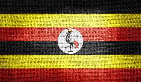 uganda: Uganda flag on burlap fabric Stock Photo