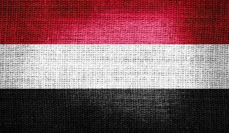 Yemen flag on burlap fabric photo