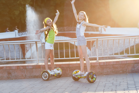 Happy girls  riding on hover board  or gyroscooter  outdoors at sunset in summer. Active life concept
