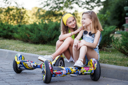 Happy girls riding on hover boards or gyroscooters outdoors at sunset in summer. Active life concept