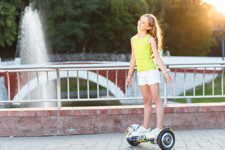 Happy girl riding on hover board or gyroscooter outdoors at sunset in summer. Active life concept Banco de Imagens