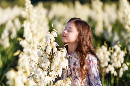 A portrait of a cute little girlwith long hair in outside at sunset in the field of white yucca flowers having fun