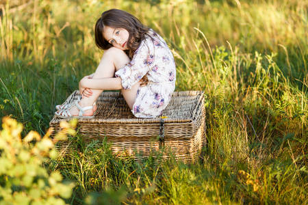 A portrait of a sad cute little girl west sitting on a basket outside at sunset Foto de archivo