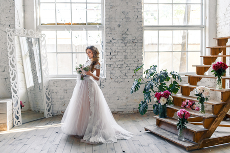 A bride with hairstyle and make up in gorgeous pink wedding dress and a vail with a bouquet of peonies. Banco de Imagens