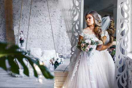 A bride with hairstyle and make up in gorgeous pink wedding dress and a vail with a bouquet of peonies. Stock fotó