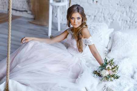 A bride with hairstyle and make up in gorgeous pink wedding dress and a vail with a bouquet of peonies. Фото со стока