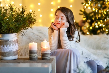 A brunette gilr in front of fur-tree and fireplace with candles and gifts. A girl dreaming. New year's eve. Christmas eve. Cozy holiday at the fur-tree with lights and gold decor.