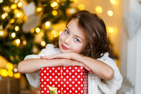 A brunette gilr in front of fur-tree and fireplace with candles and gifts. A surprised girl. A girl dreaming. New years eve. Christmas eve. Cozy holiday at the fur-tree with lights and gold decor.