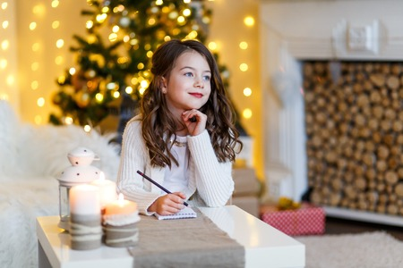 A brunette gilr in front of fur-tree writing a letter to santa claus. A girl dreaming. New year's eve. Christmas eve. Cozy holiday at the fur-tree with lights and gold decor. 版權商用圖片