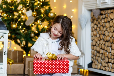 A brunette gilr in front of fur-tree and fireplace with candles and gifts. A surprised girl. A girl dreaming. New year's eve. Christmas eve. Cozy holiday at the fur-tree with lights and gold decor. 版權商用圖片
